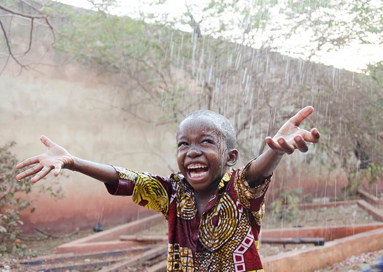 Child under the rain in Mali (photo by Riccardo Mayer).
